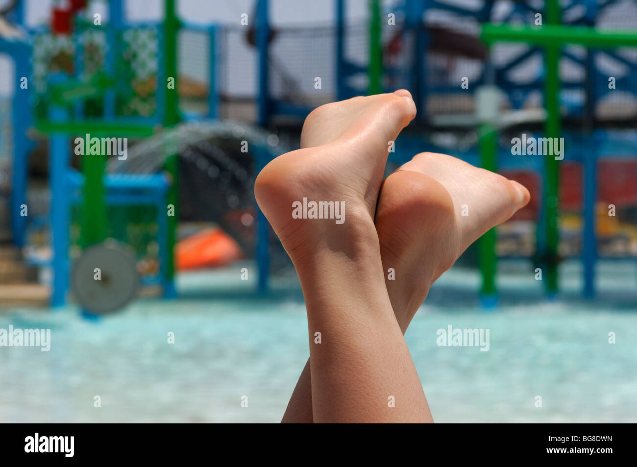 huge discount f16c8 54231 Bare feet of young woman relaxing on sunbed near a pool in a water park -