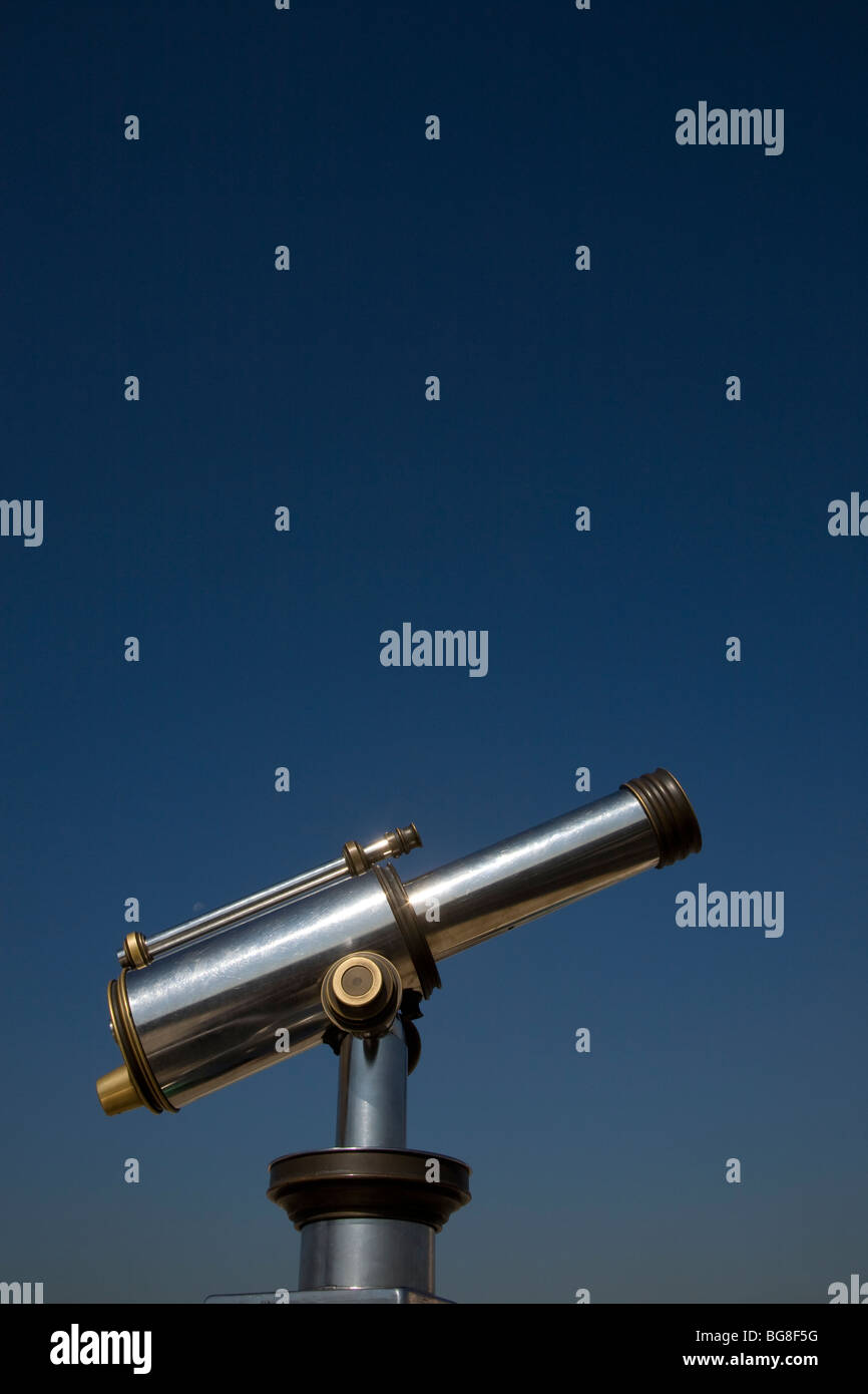 Telescope in blue sky pointing up. - Stock Image