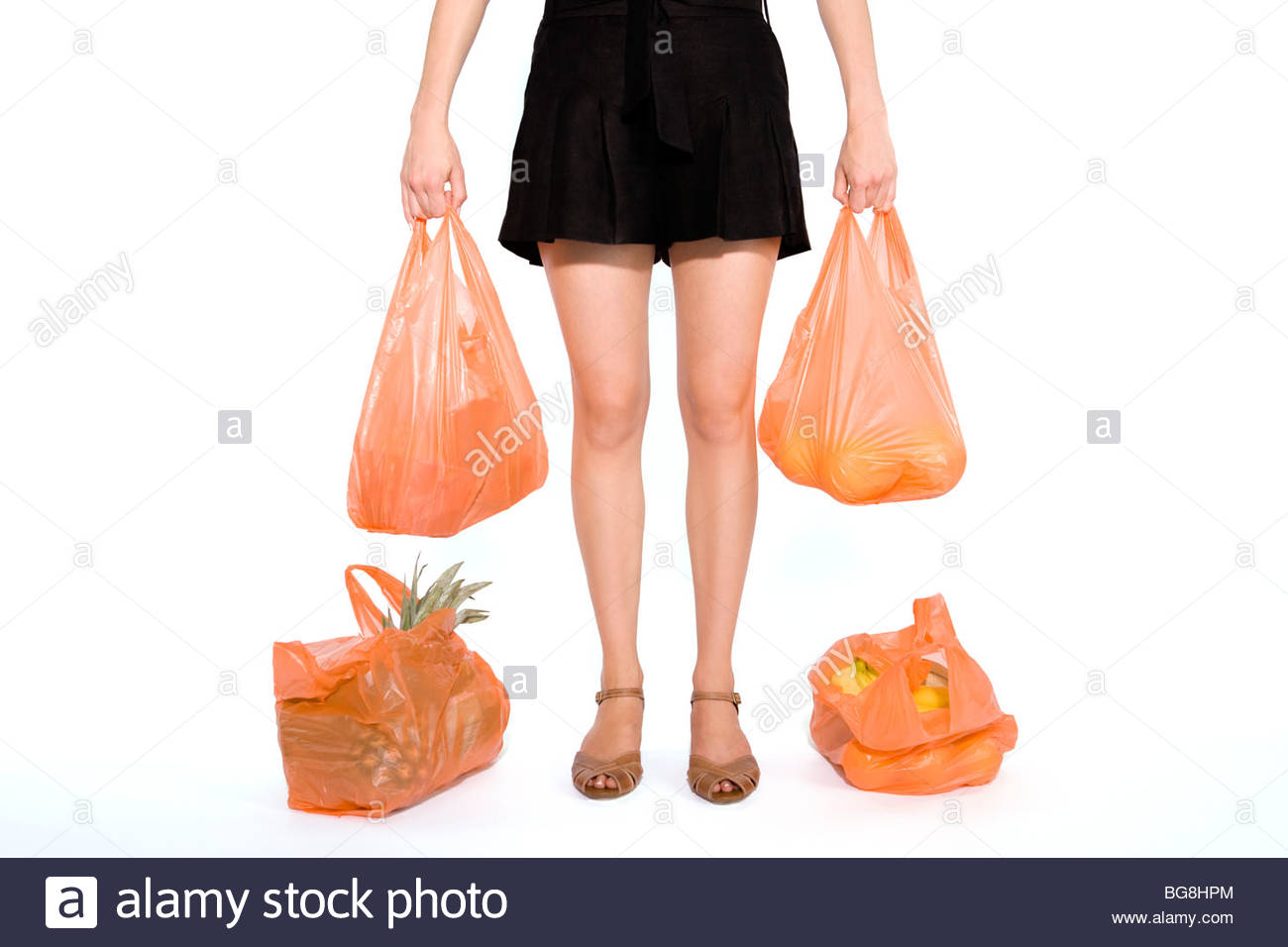 A Young Woman Carrying Heavy Shopping Bags - Stock Image