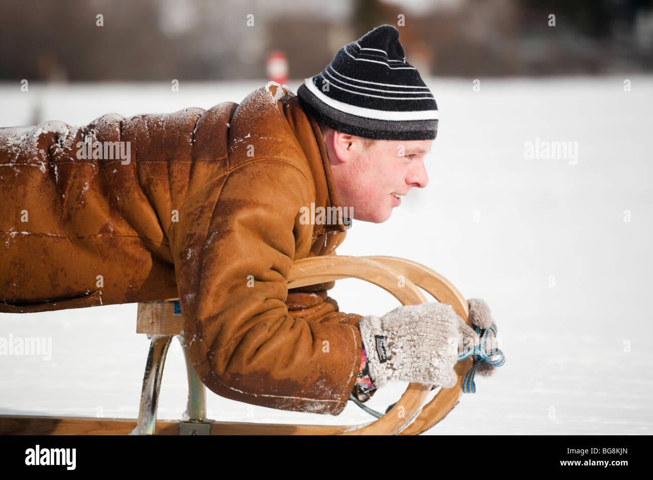 Man tobogganing on snow sledge. Rauris Austria Europe. - Stock Image
