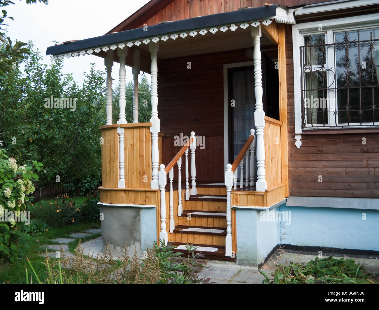The pictures shows a new wooden porch in a country house, surrounded by green trees and bushes - Stock Image