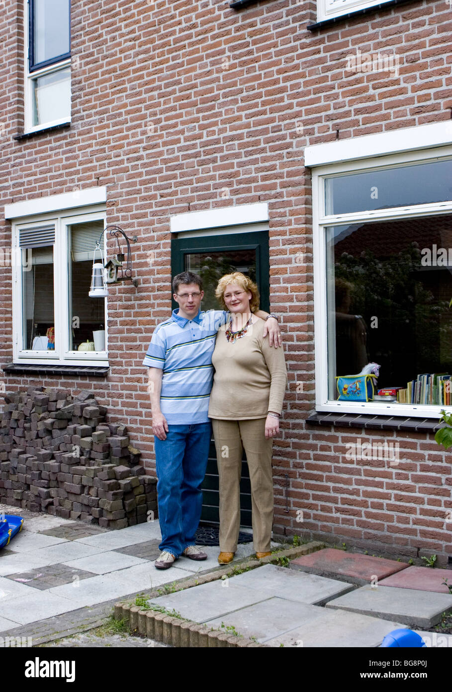 Middle class couple in front of house - SerieCVS417399d - Stock Image