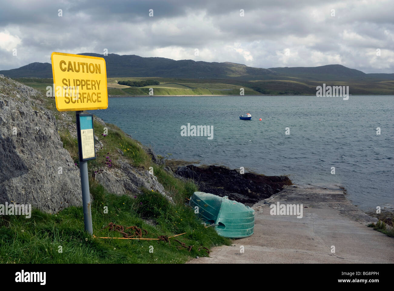 A sign warning of a slippery surface at East Keoldale pier, in the far north-west of Scotland - Stock Image
