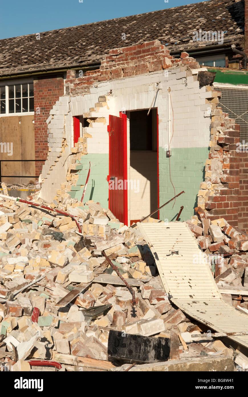 Red door and broken wall at school under demolition - Stock Image