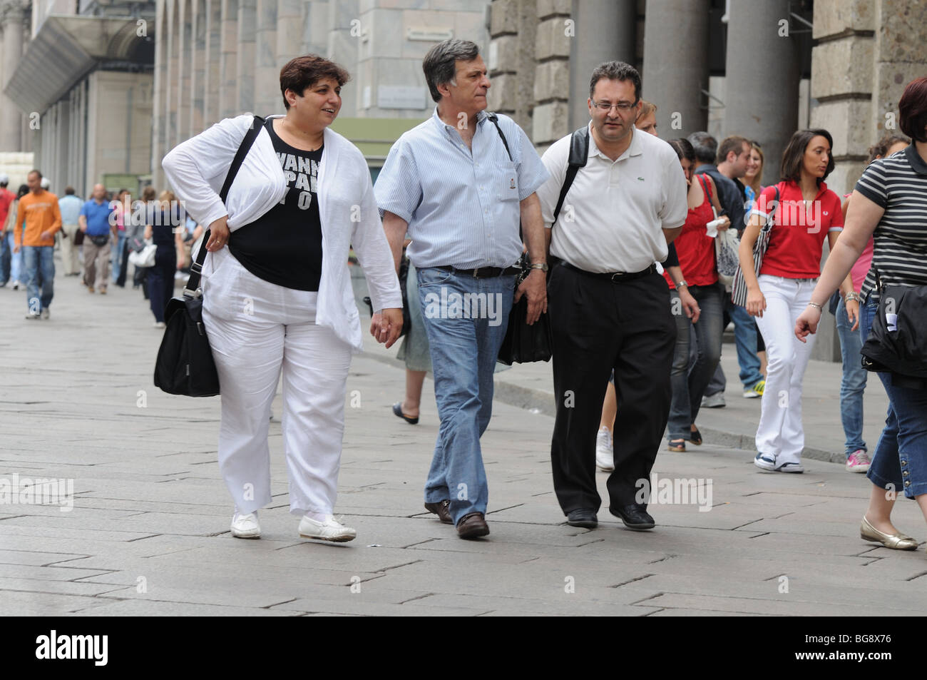 Three overweight visitors carrying shoulder bags on side of Piazza del Duomo Milan Milano Italy Italia - Stock Image