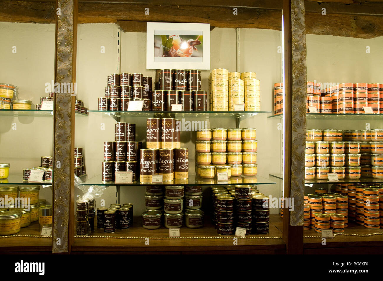 A variety of poultry products, foie gras paramount, displayed for sale in a French farm's boutique showcase - Stock Image