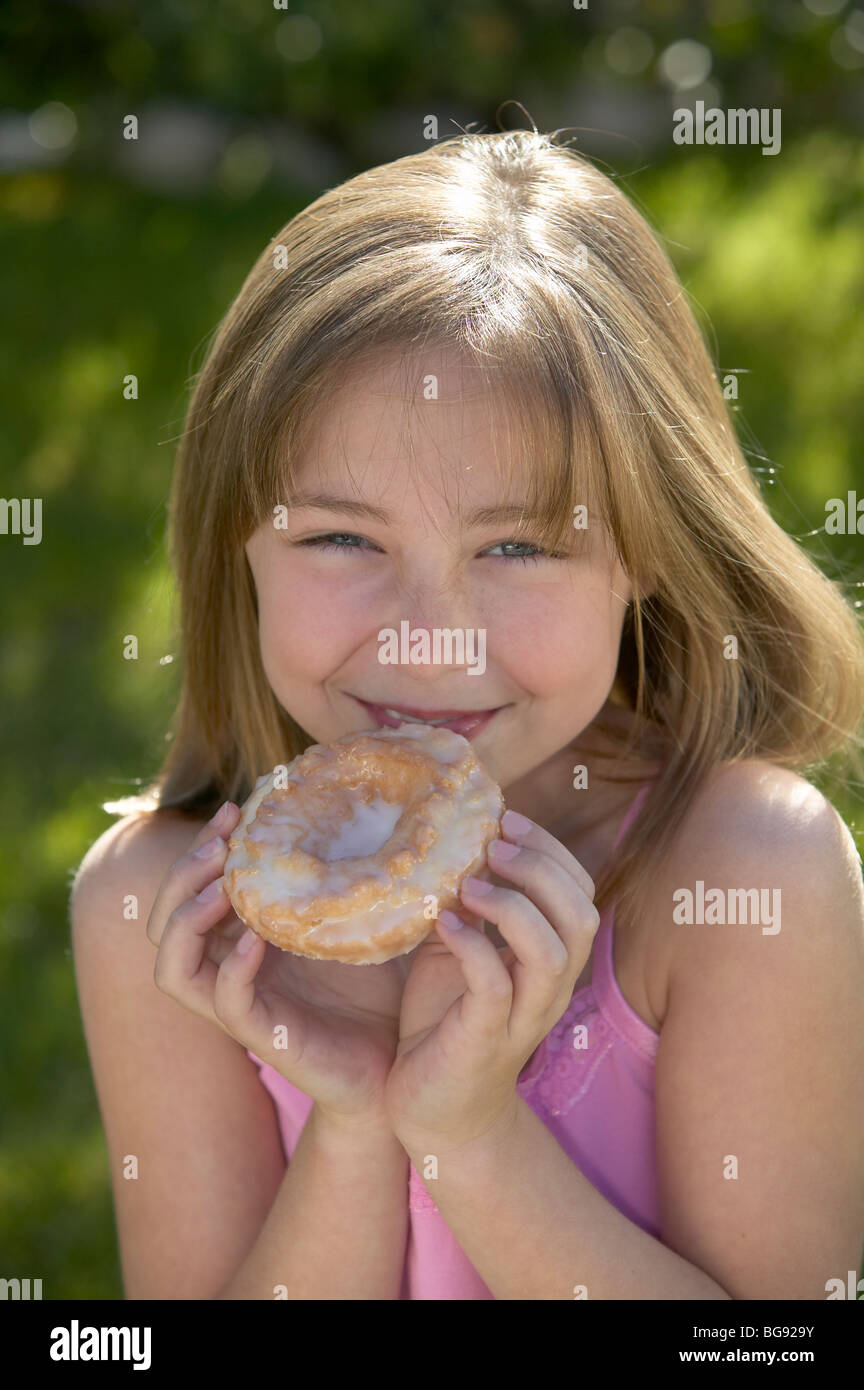 Girl holding old fashioned donut outside - Stock Image