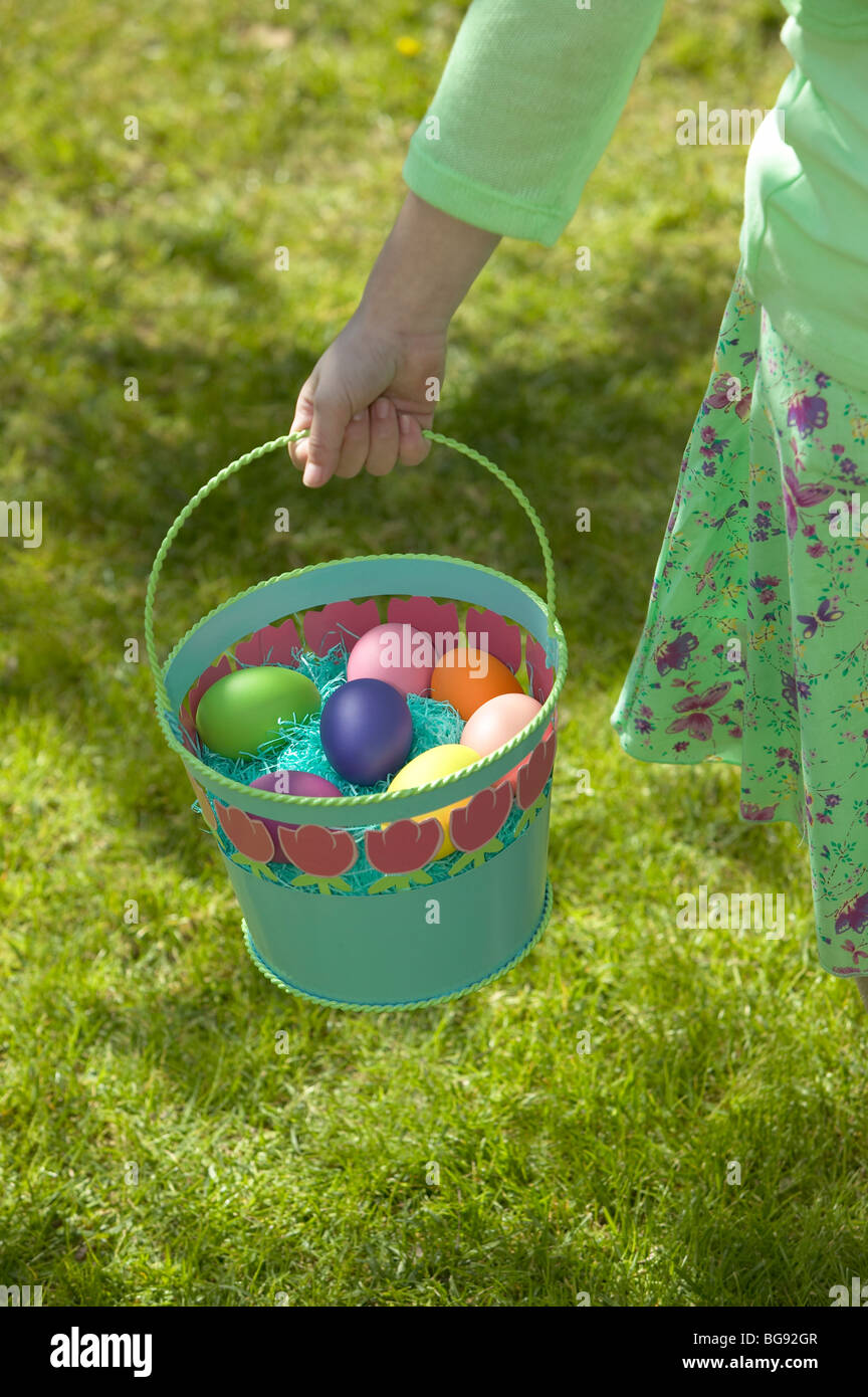 Girl holding Easter egg basket while walking on lawn - Stock Image