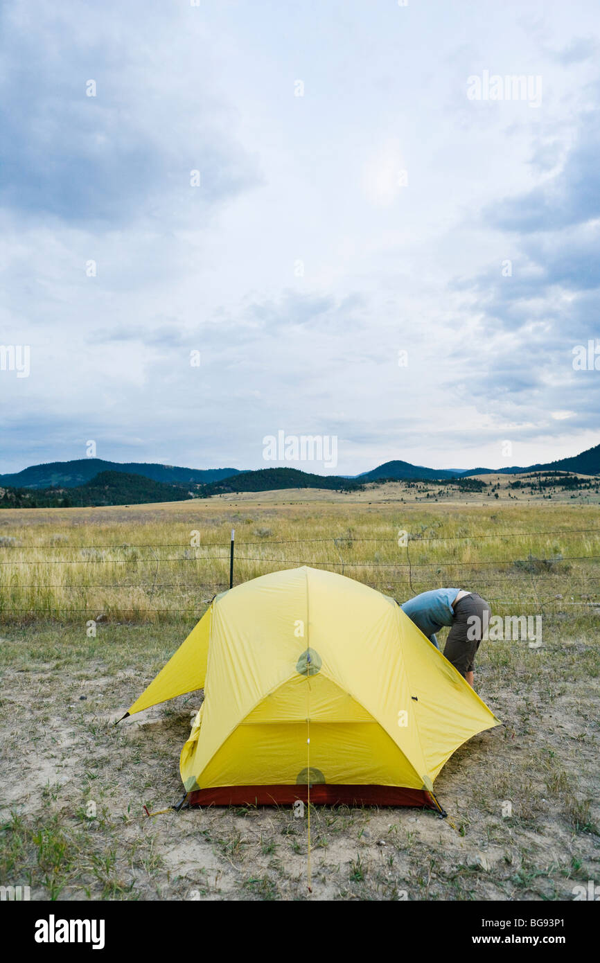 Camper bending over to get in a tent. Southwest Montana near Fairview Hot Springs. - Stock Image