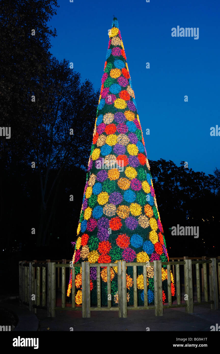 A glowing colourful Christmas tree - Stock Image