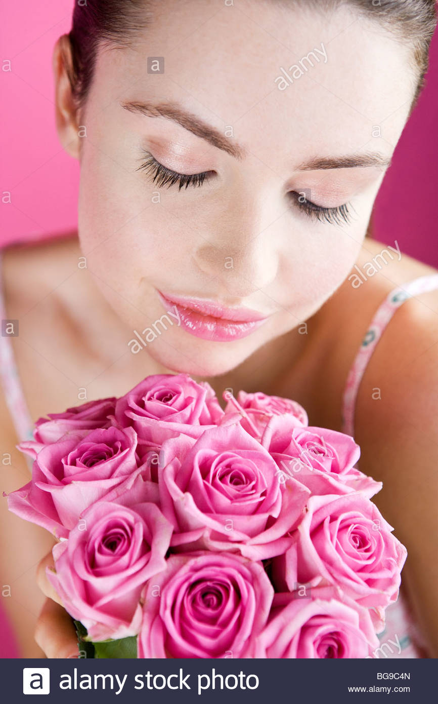 A Young Woman Smelling A Bunch of Pink Roses - Stock Image