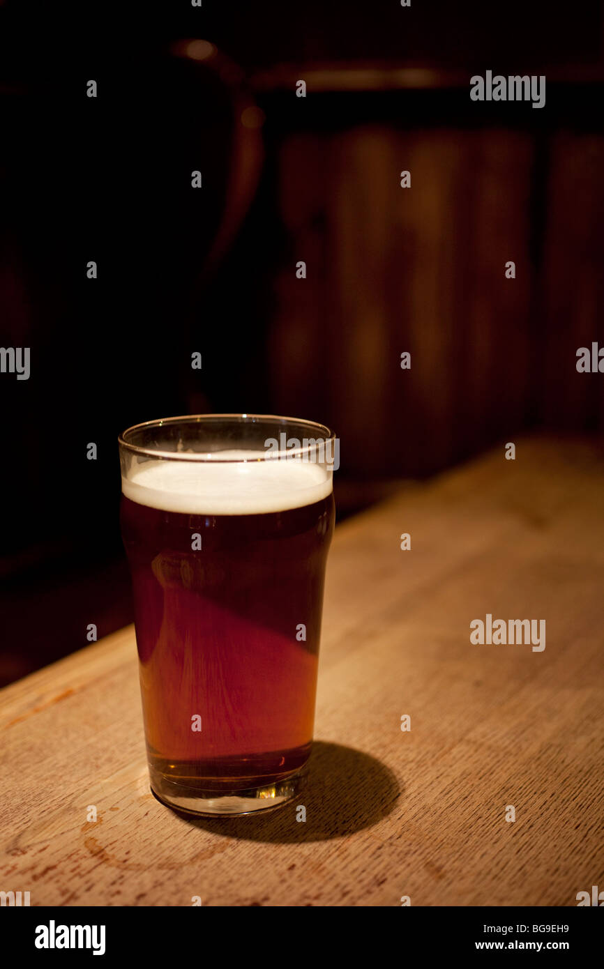 Pint glass of real ale on a pub table. Sales of ales are increasing, where other beer and beverages are declining. Stock Photo