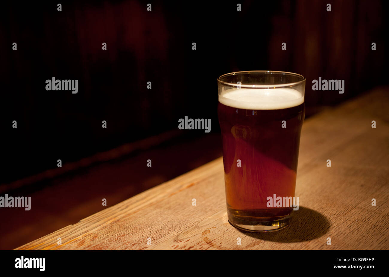 Pint glass of real ale on a pub table. - Stock Image