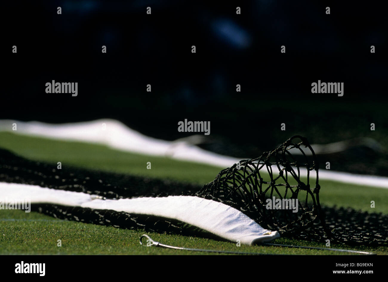 Dismantled tennis net on a grass court - Stock Image