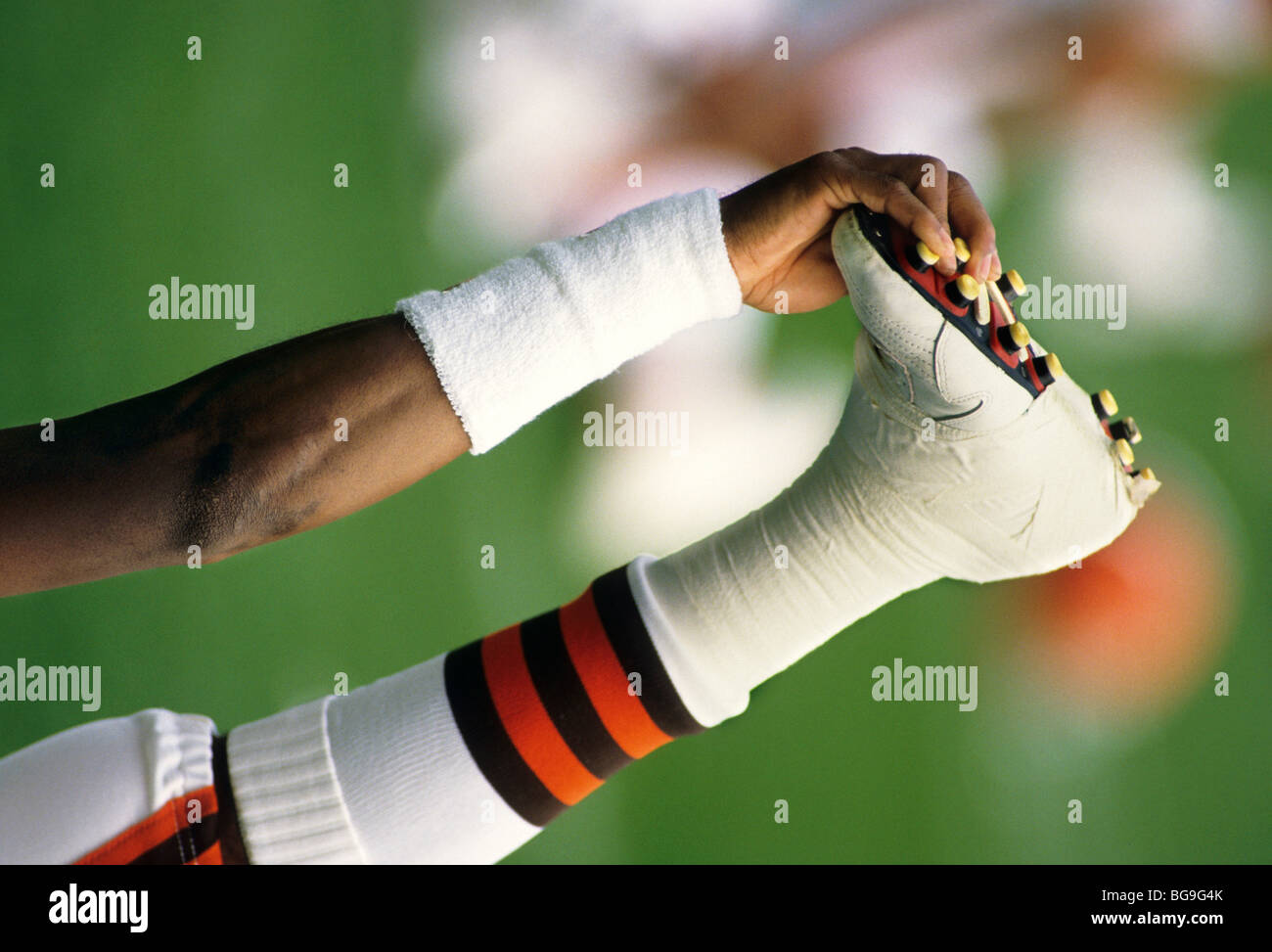 American football player stretches out his taped ankle before a game - Stock Image