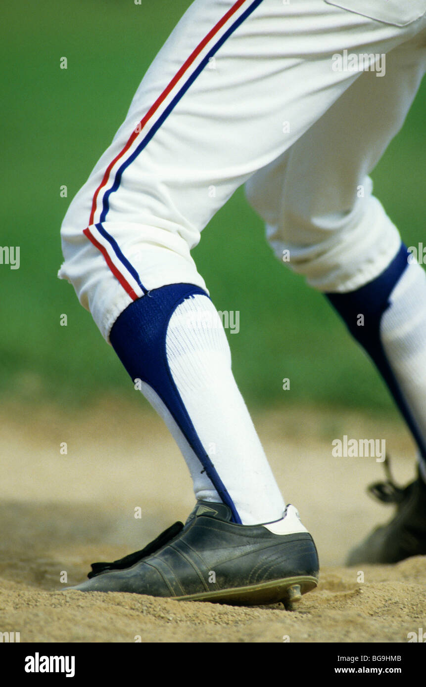 Baseball player standing with foot wedged in sand - Stock Image