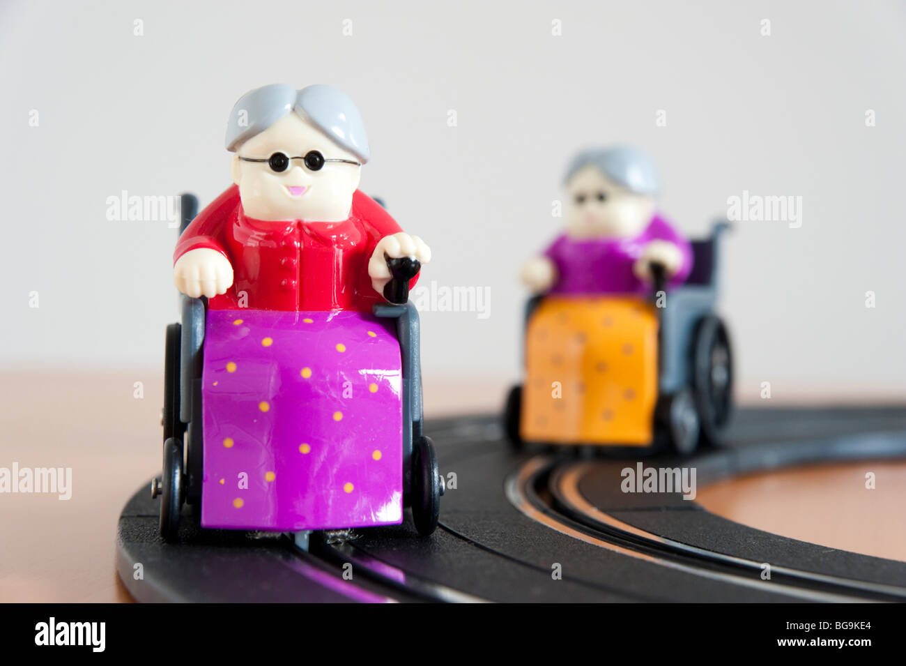 Scalextric imitation of active elderly women racing round track - Stock Image
