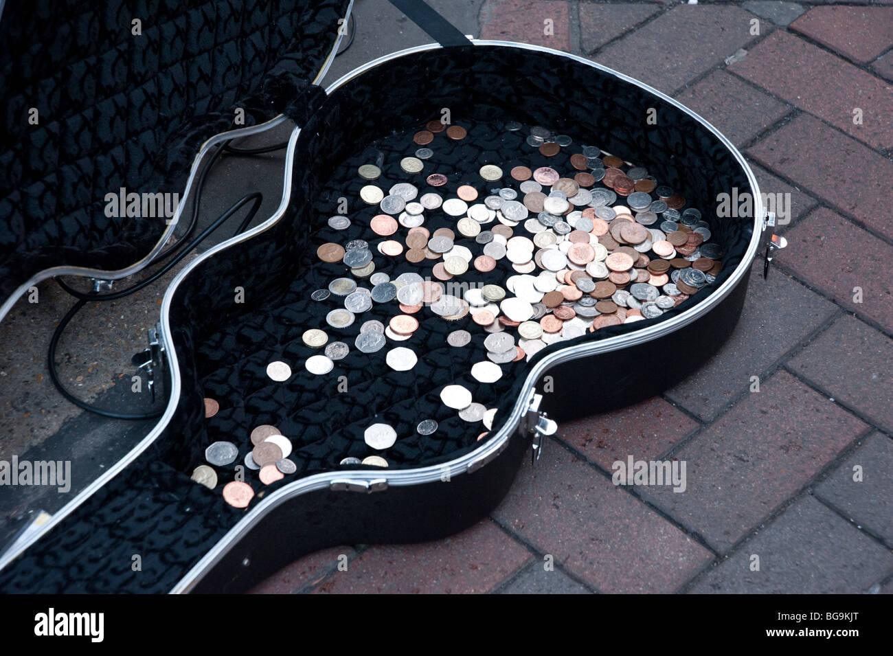 Coins in busker's guitar case, London, England, UK - Stock Image