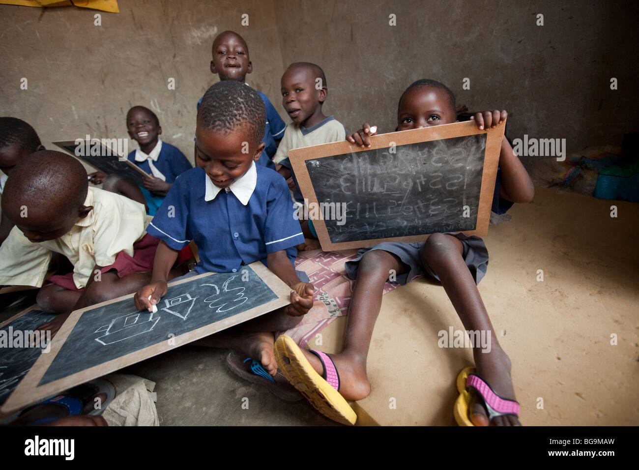 Young children draw on blackboards in an orphanage in Amuria, Uganda, East Africa. - Stock Image