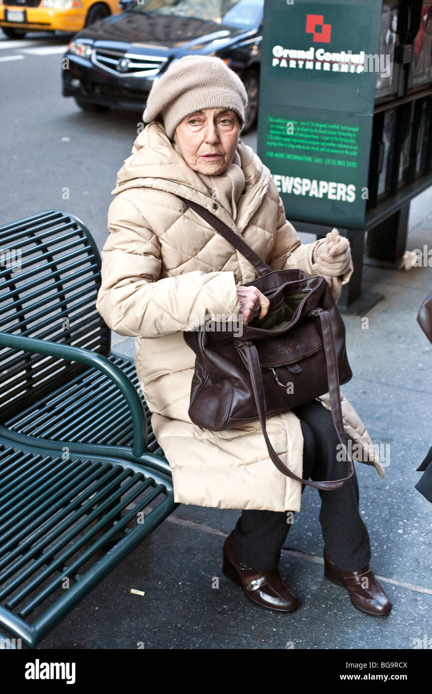 elegant warmly dressed stylish old lady pauses on a Fifth Avenue bench in Midtown Manhattan - Stock Image