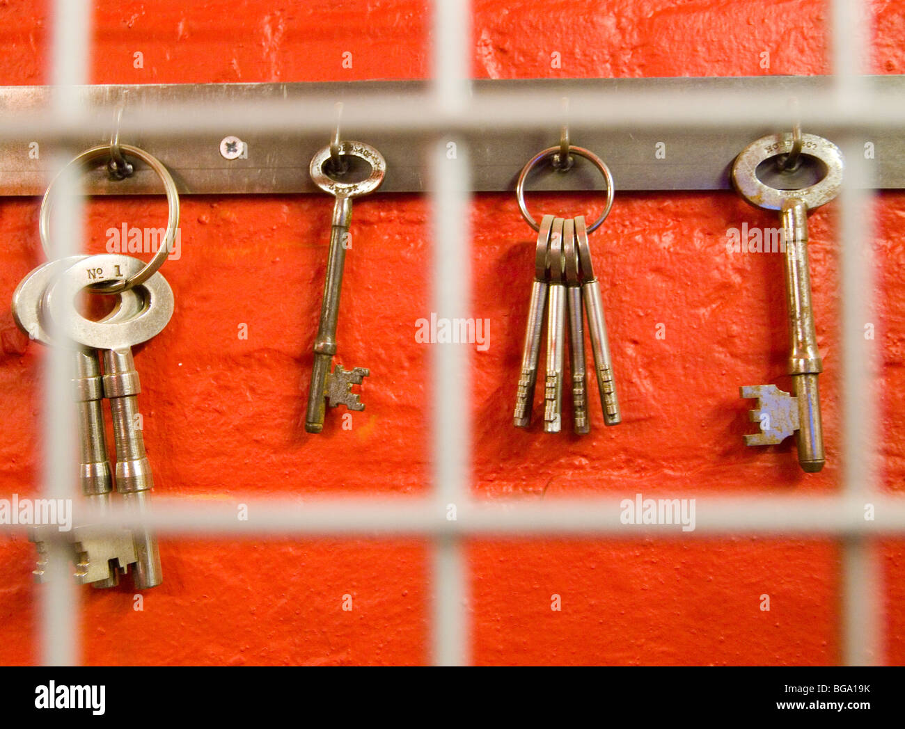 A row of metal keys, hanging up and locked away behind a mesh door. - Stock Image
