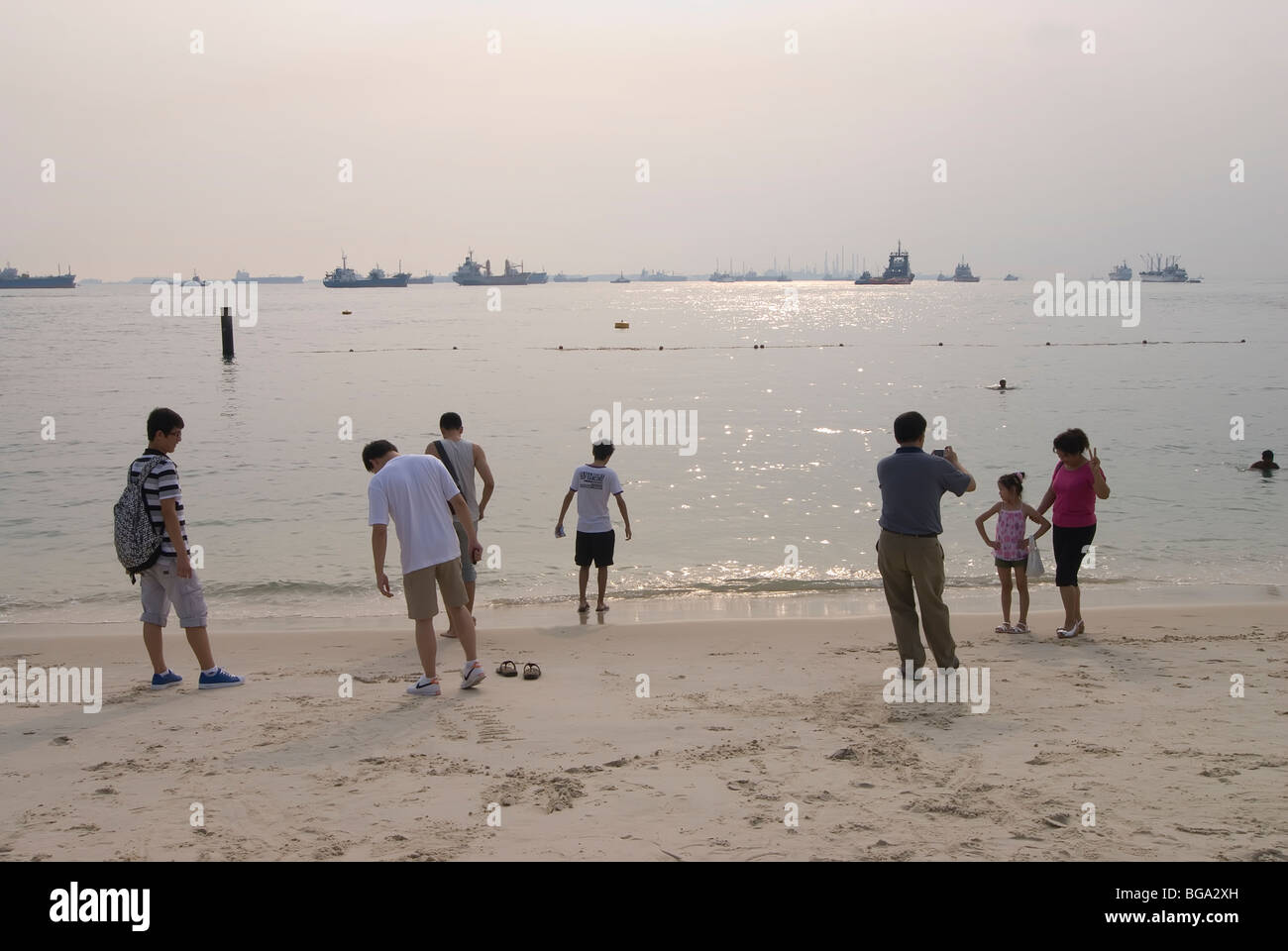 People at the edge of the sea on the beach on Sentosa Island off Singapore - Stock Image