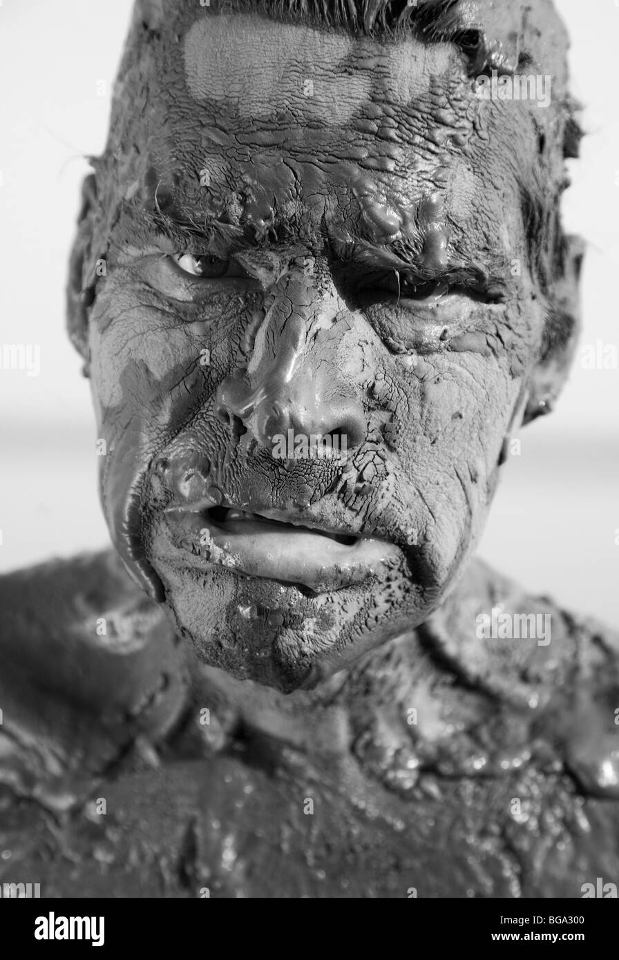 Man's face is very dirty in the mud. Dirt is not curative - Stock Image