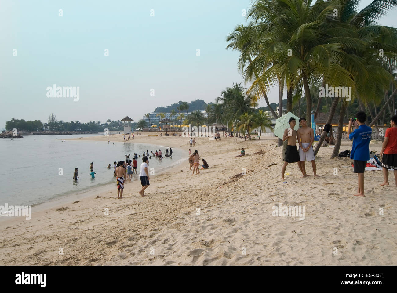 Sentosa Island beach off Singapore with people posing for a photographer holding an umbrella - Stock Image