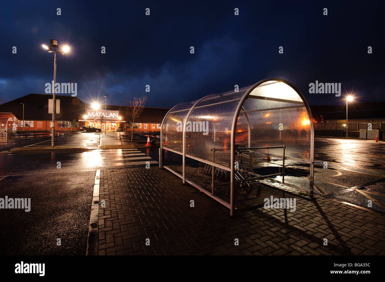 deserted shopping mall retail park centre and car park at night, Aberystwyth Wales UK - Stock Image