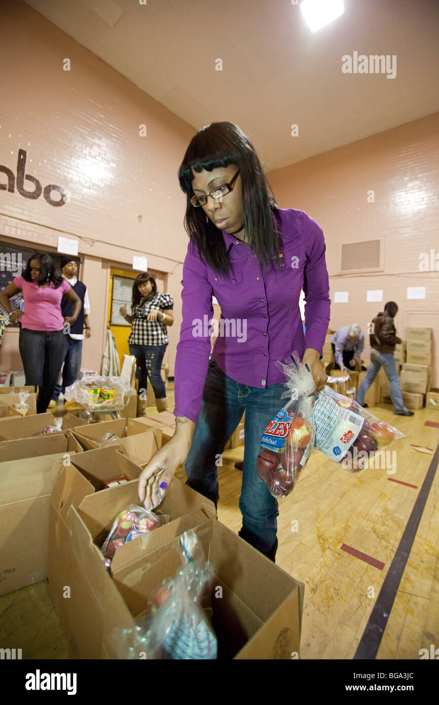 High school students and teachers pack food for the needy - Stock Image