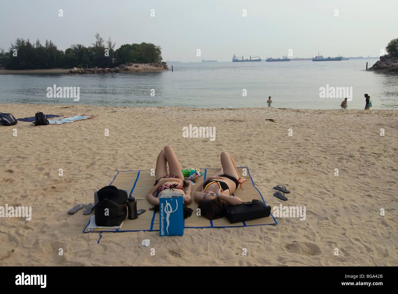 Sentosa Island beach off Singapore with two girls sunbathing in bikinis - Stock Image
