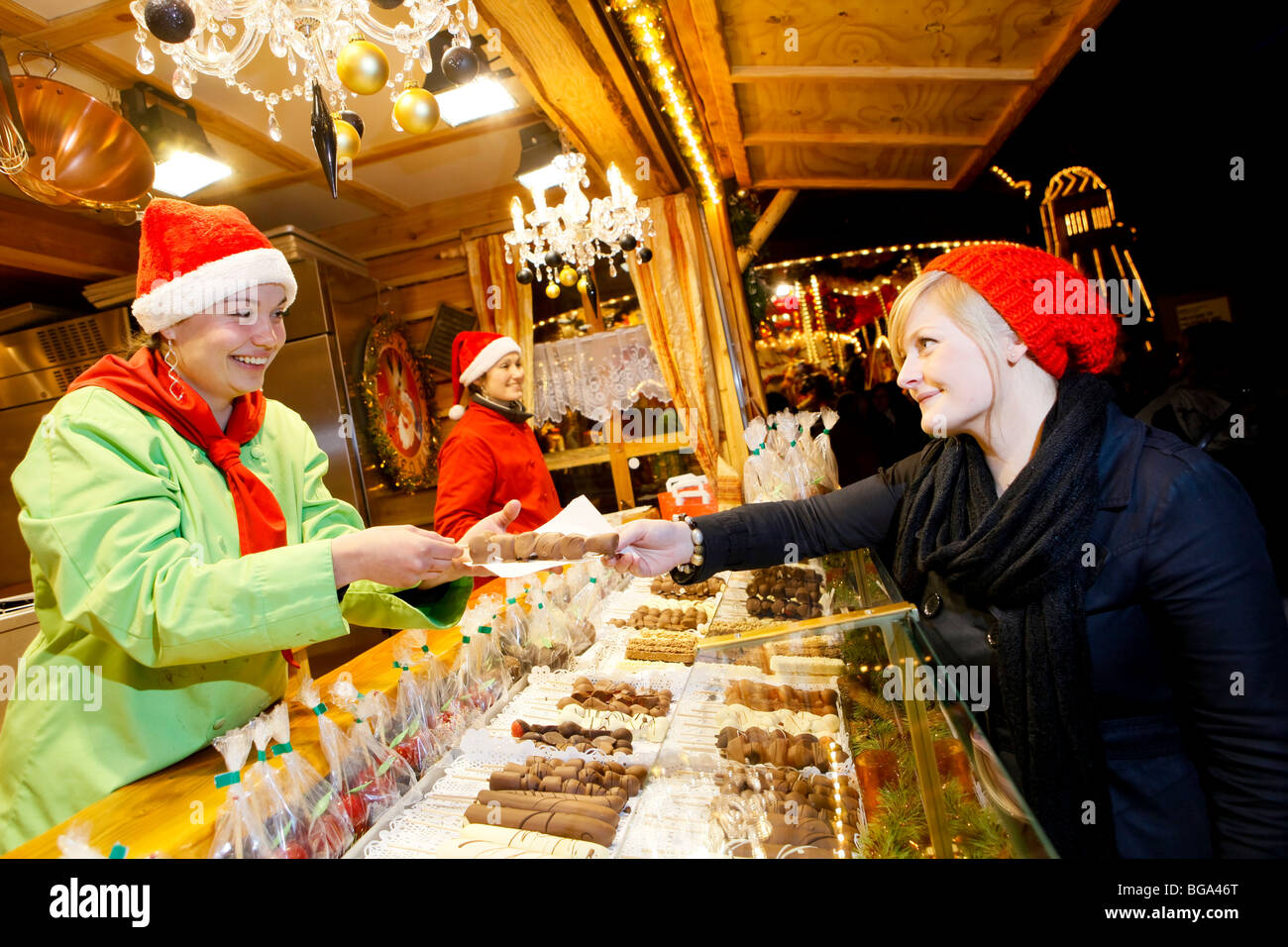 The German Market in Bimingham City Centre at Christmas. Buying handmade chocolate at a stall in the market. - Stock Image