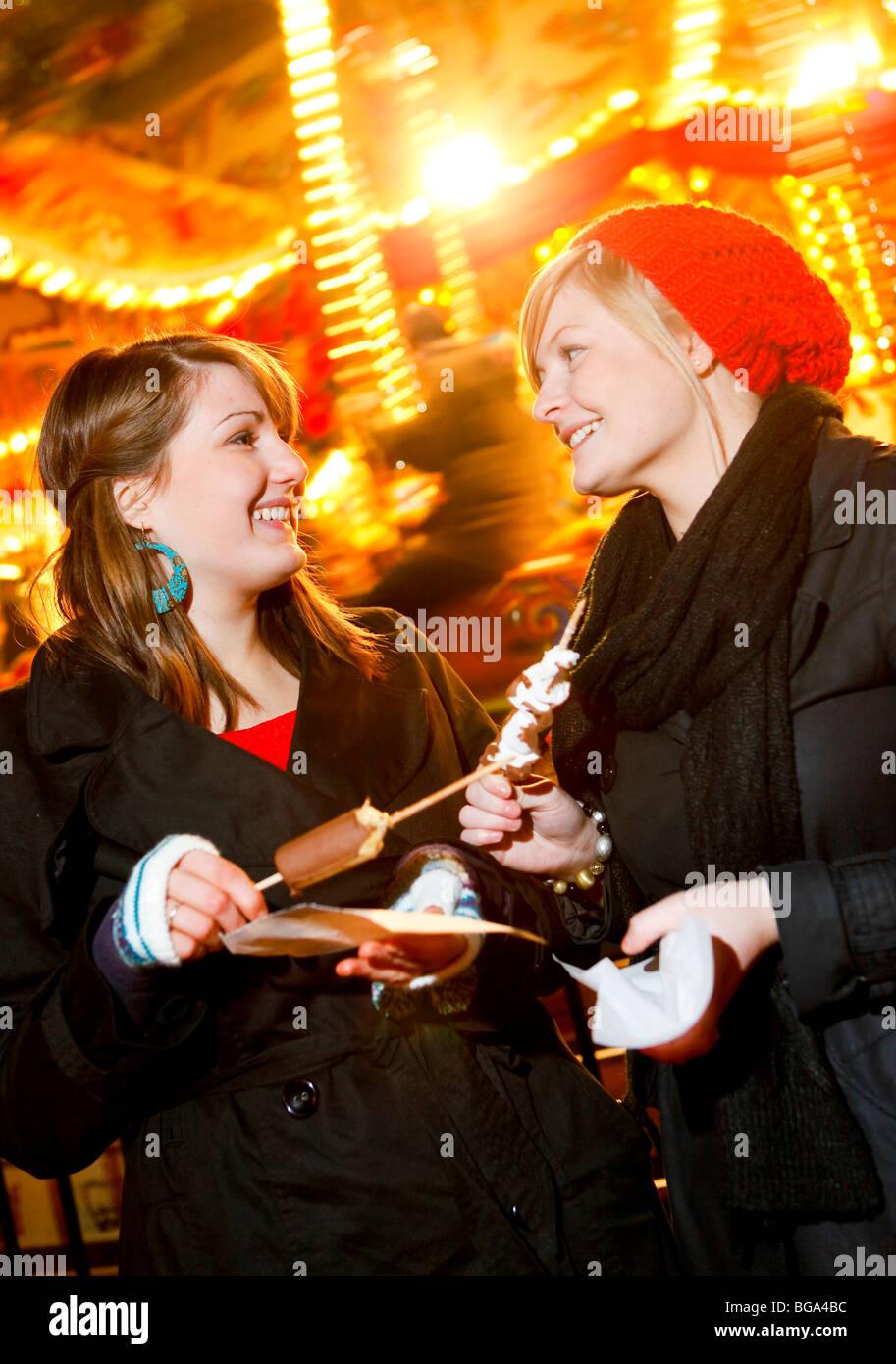 The German Market in Bimingham City Centre at Christmas. Two young women next to the carousel in the market. - Stock Image