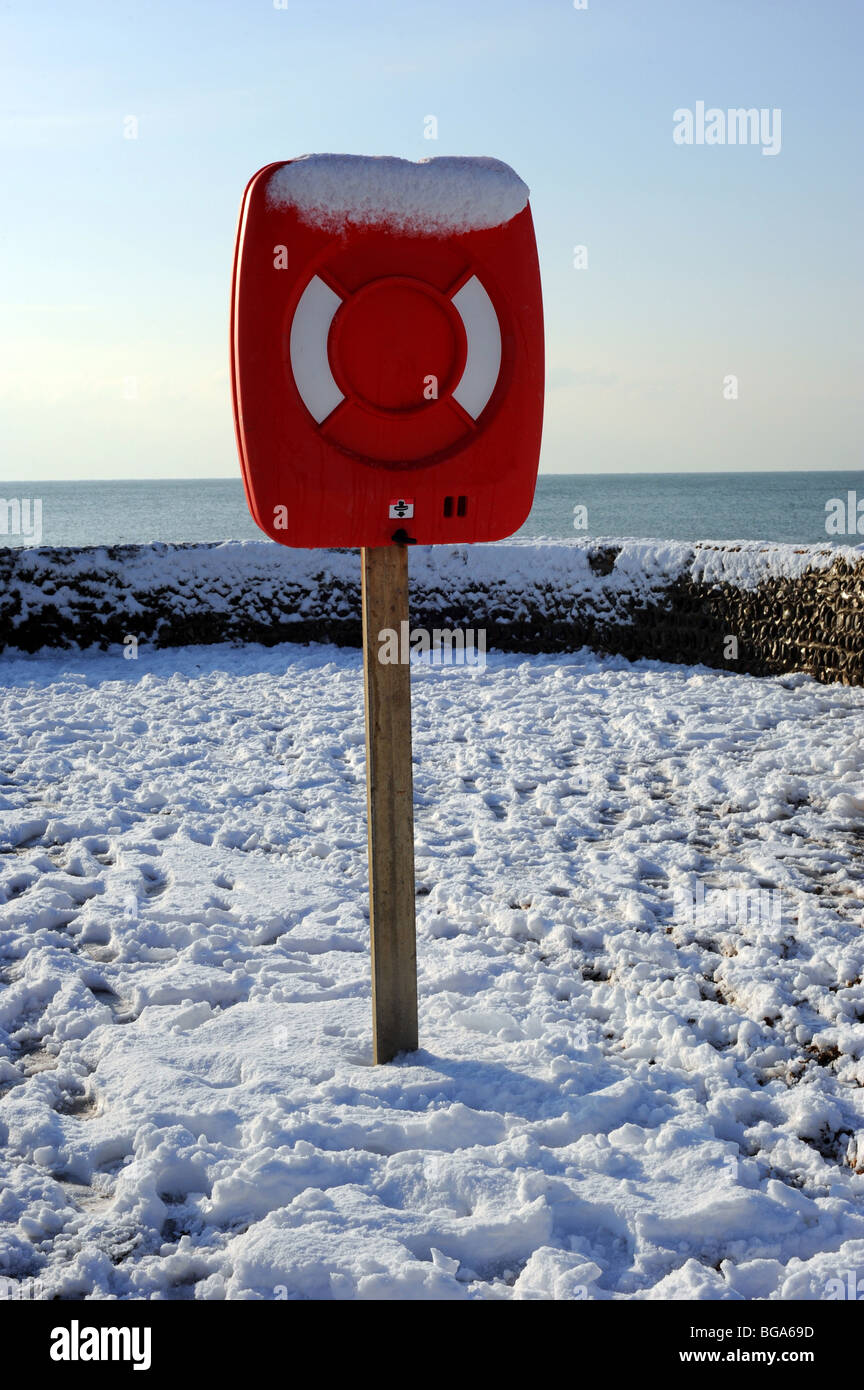 Red lifebelt covered in snow on brighton beach - Stock Image