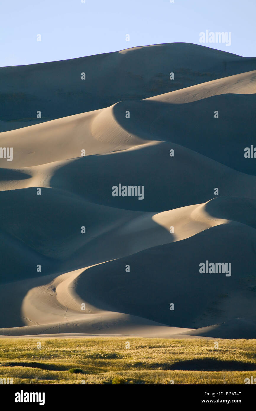 Sand moved by wind collects up against the Rocky Mountains forming Great Sand Dunes National Park, Colorado - Stock Image