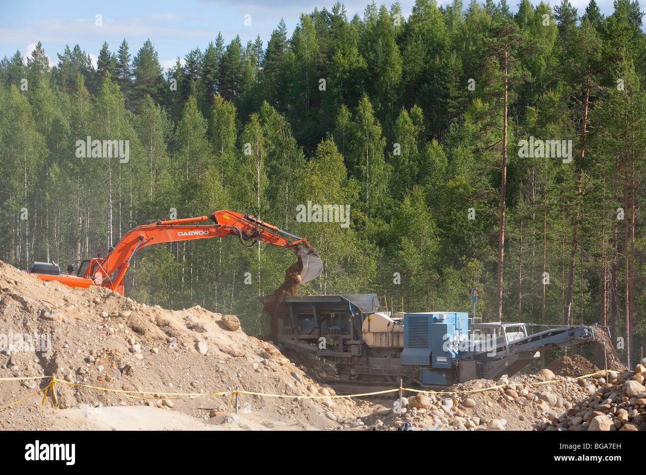 Digger loading sand and stones to the crusher / separator machine in a gravel pit , Finland - Stock Image