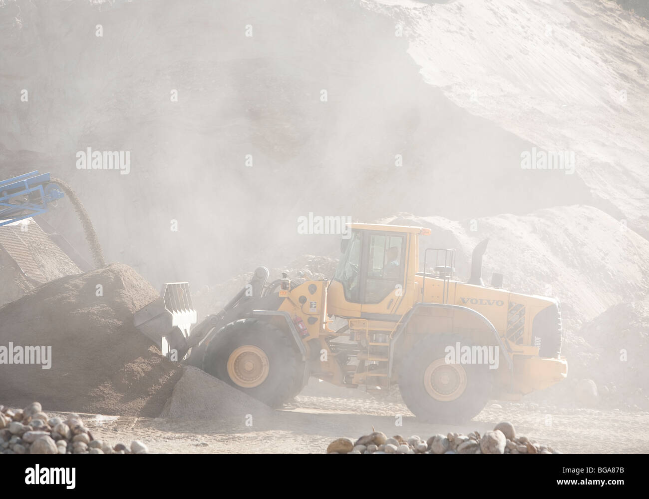 Front loader moving sand and grit in a sandpit - Stock Image