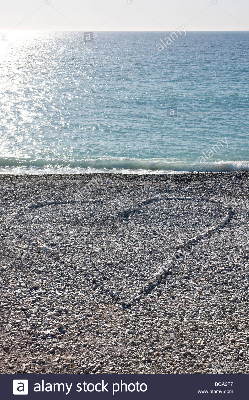 Love heart made of pebbles on the beach at Baie des Anges, Nice - Stock Image