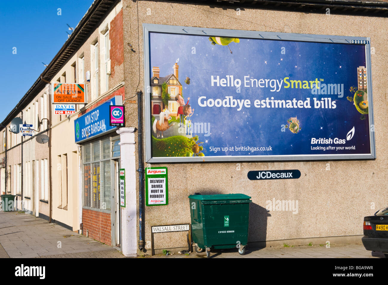JC Decaux billboard site featuring poster for British Gas on end wall of corner shop in Newport South Wales UK - Stock Image