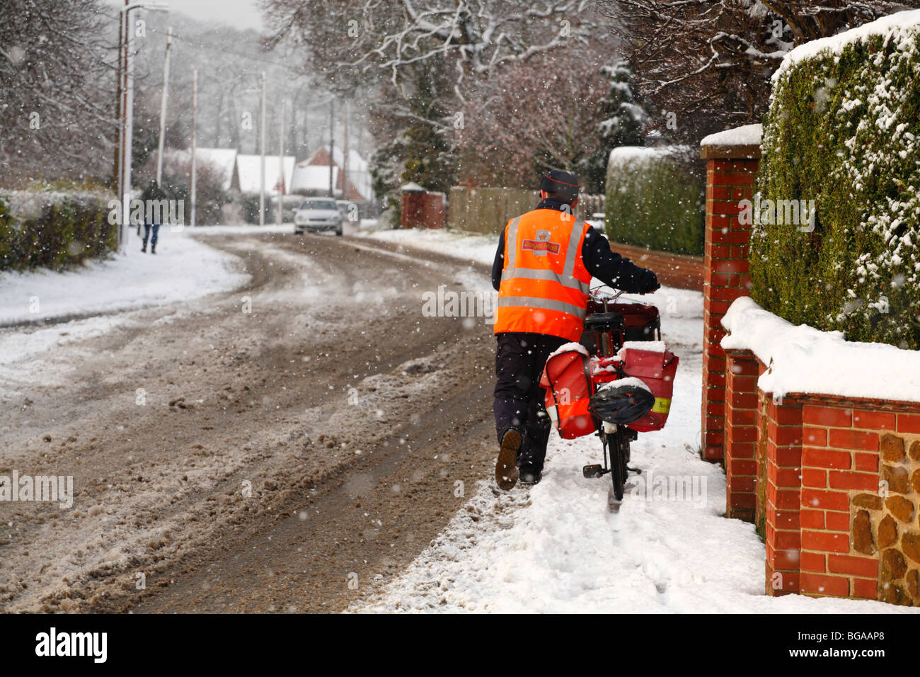 A postman struggles through the snow with his bicycle to deliver the Christmas post. - Stock Image