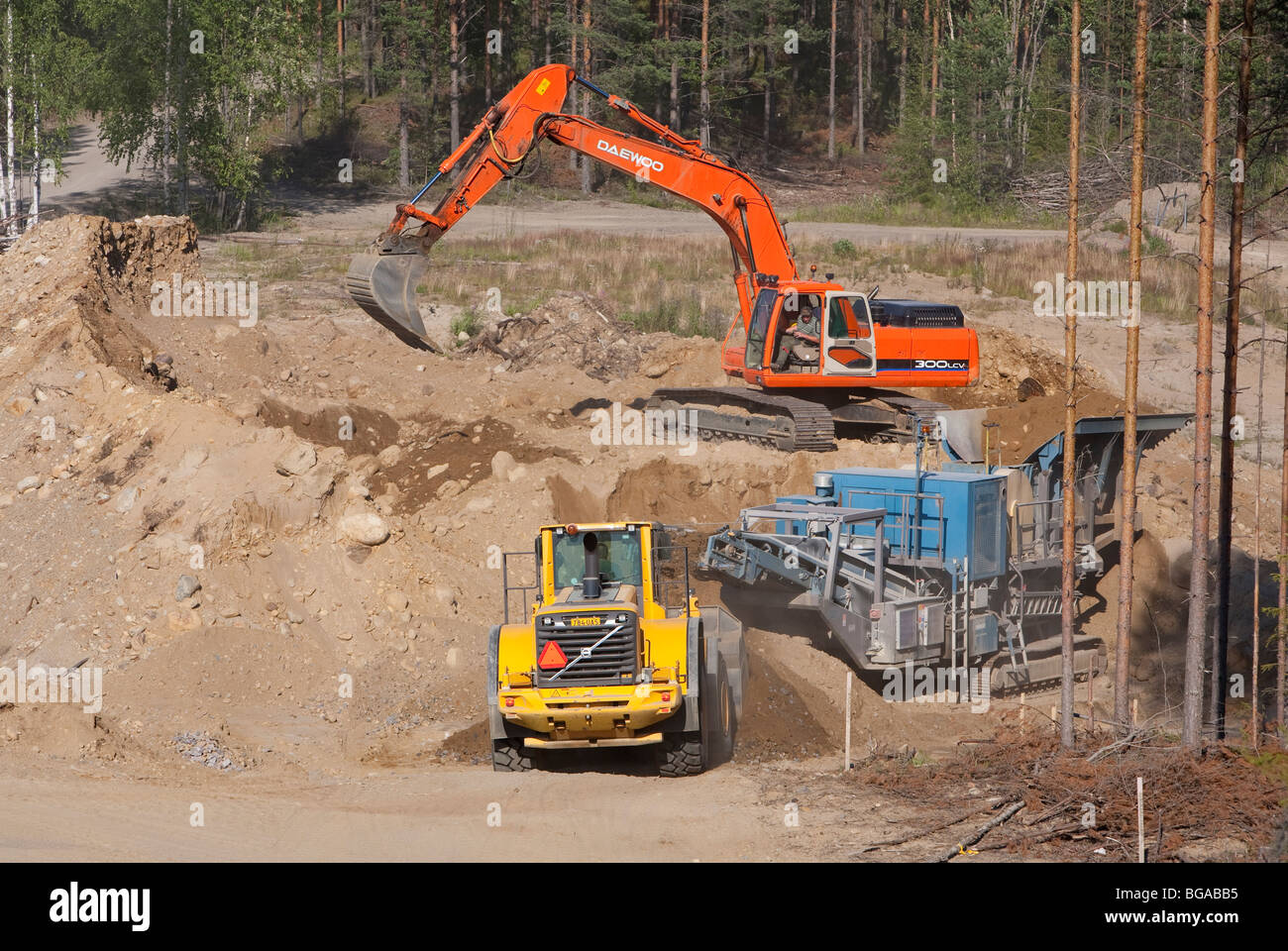 Production at sandpit; digger loads stones soil to crusher / separator and front loader , Finland - Stock Image