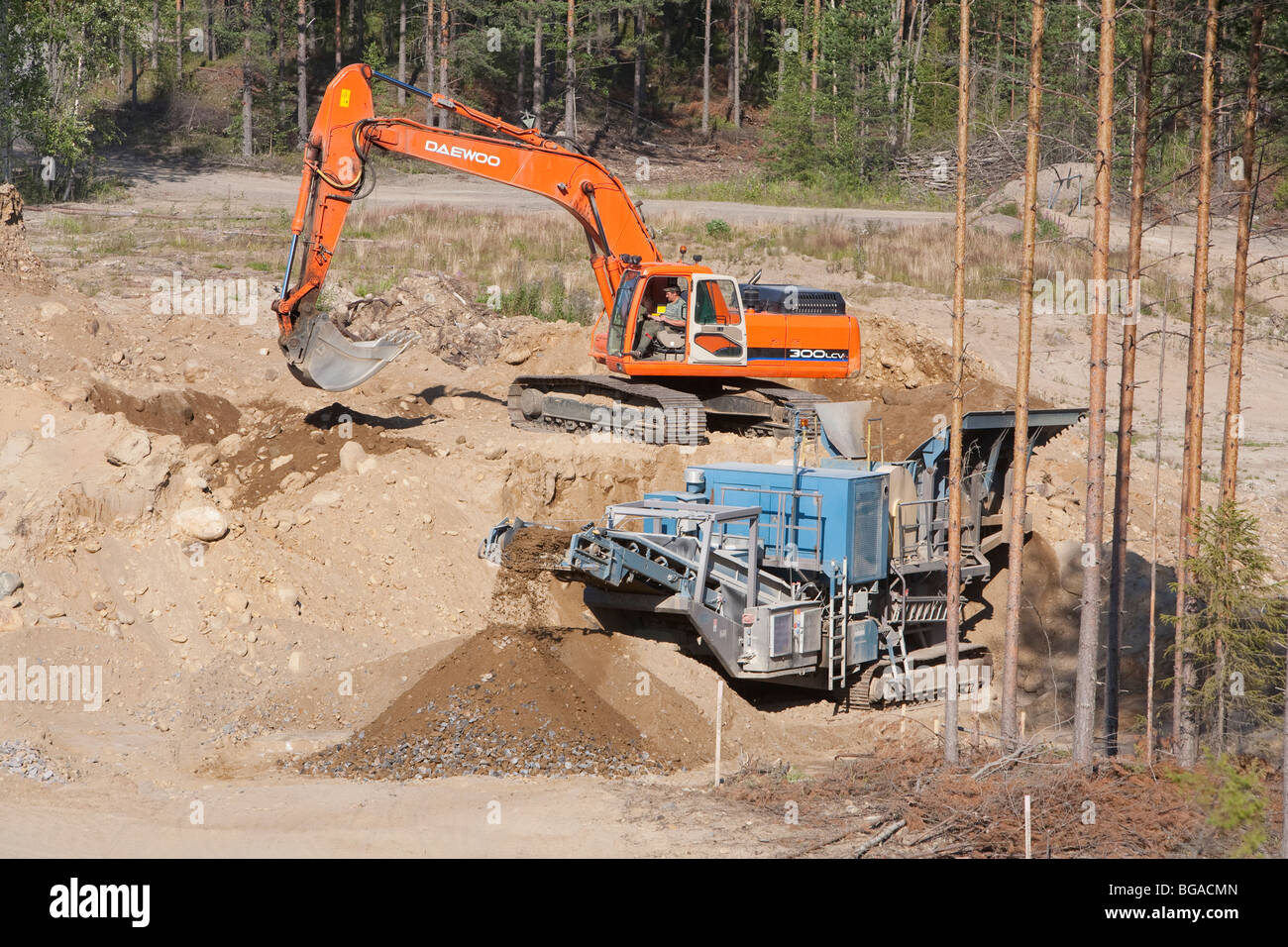 Daewoo digger loading sand and stones to the rock crusher / separator machine at a sandpit , Finland - Stock Image