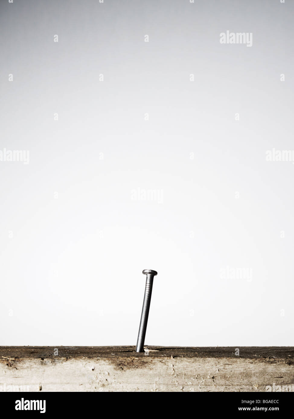 Nail sticking out of wooden board Stock Photo