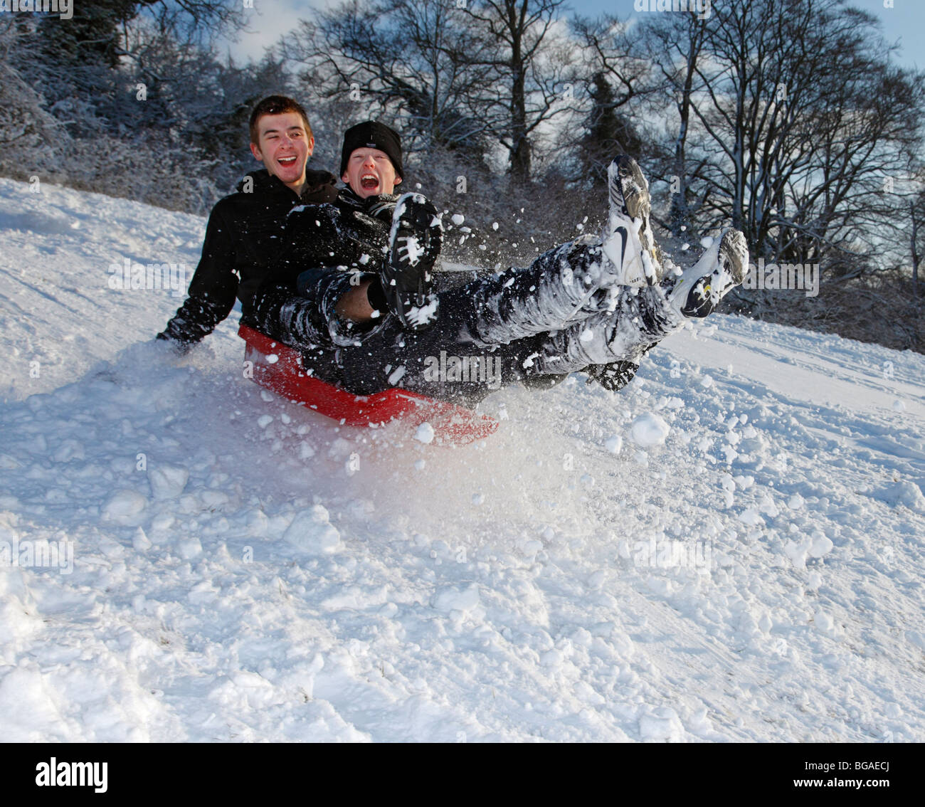 Two Teenagers sledging. Stock Photo