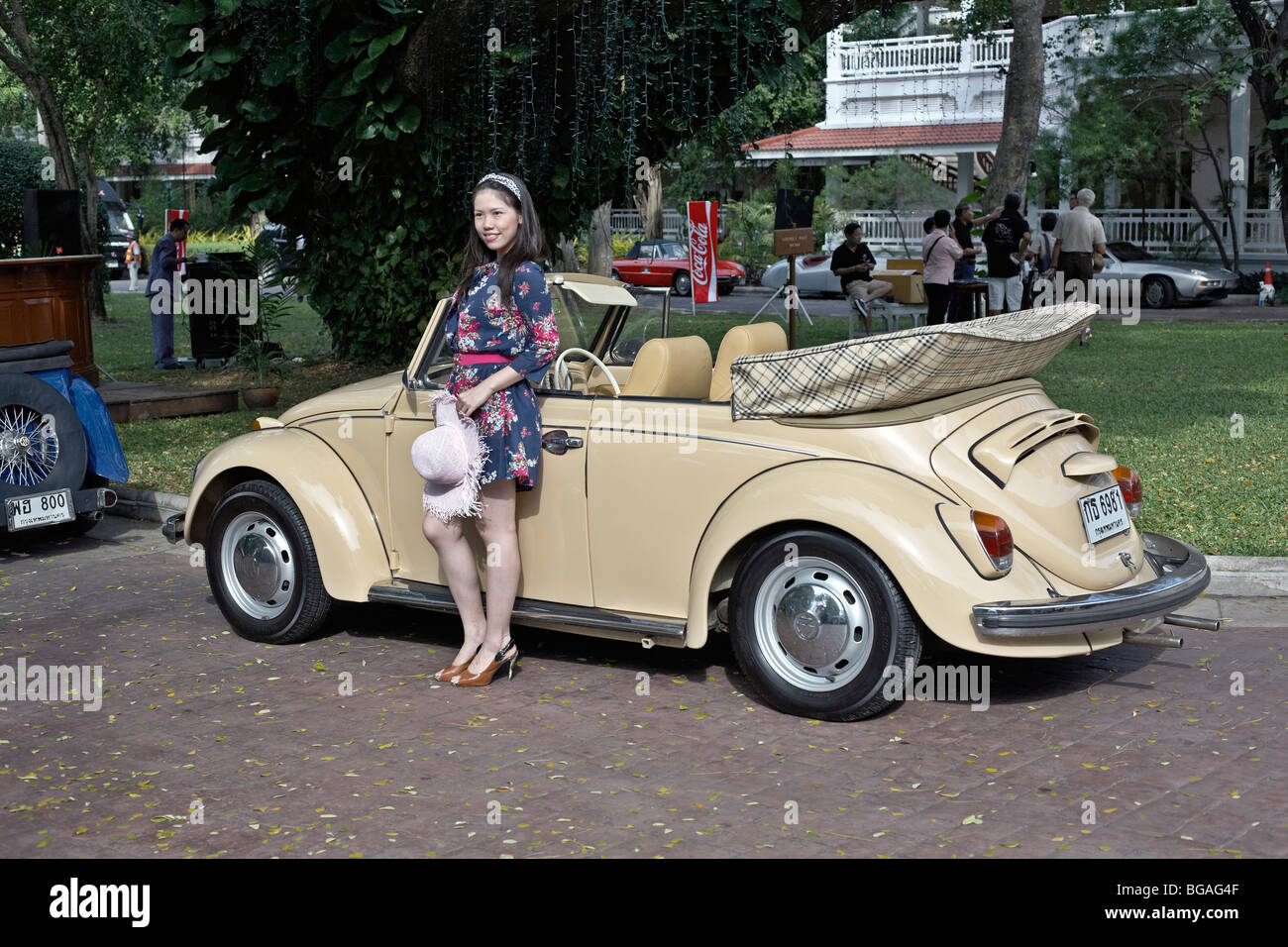 Female model posing with a classic cream Volkswagen Beetle convertible motor car. Thailand S. E. Asia - Stock Image