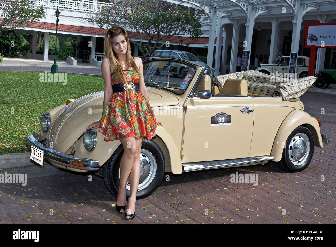 Female model posing with a classic cream coloured Volkswagen Beetle convertible motor car. Thailand S. E. Asia - Stock Image