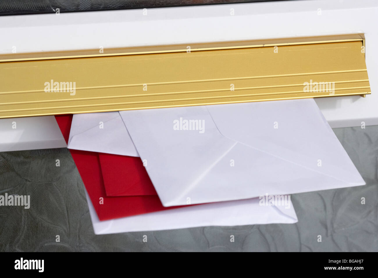 letters and cards sticking out of the letterbox of a house in the uk - Stock Image