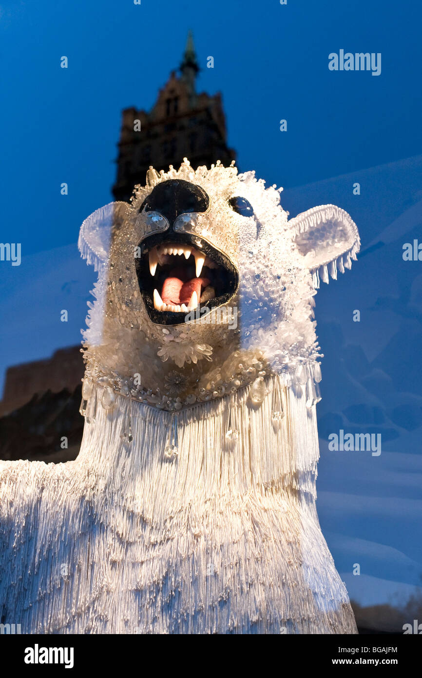 a menacing but magical polar bear wearing crystal mask in a Bergdorf Goodman Christmas window refecting the Sherry - Stock Image