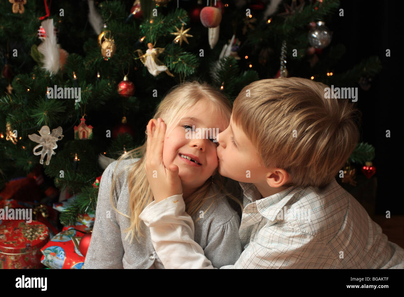 Young boy giving his little sister a kiss in front of a christmas ...