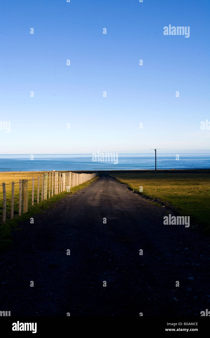 Fenced lined gravel road towards ocean with blue skies - Stock Image